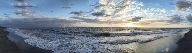 Toneel panoramische zonsondergang bij het overzees in gouden uur met ontzag bewolkte hemel in een koude de winterdag in de Roman  stock afbeelding