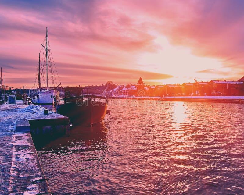 Toneel rode purpere en violette zonsondergang over plattelandsrivier in Europa met oude schepen die rust hebben bij de sneeuwhave royalty-vrije stock fotografie