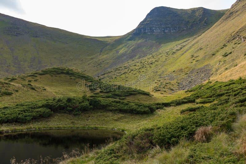Toneelbergmeer met groen gras en blauwe sluw Natuurlijke vijver in heuvels Platteland en valleiachtergrond stock foto