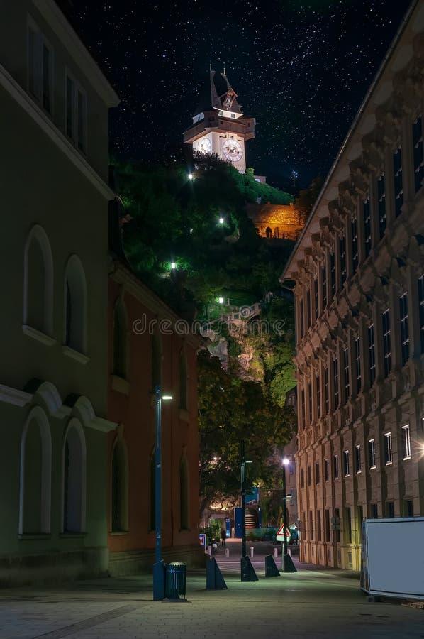 Toneelcityscape van Schlossberg en Grazer Uhrturm - klokketoren, Graz, Oostenrijk bij sterrige nacht royalty-vrije stock foto