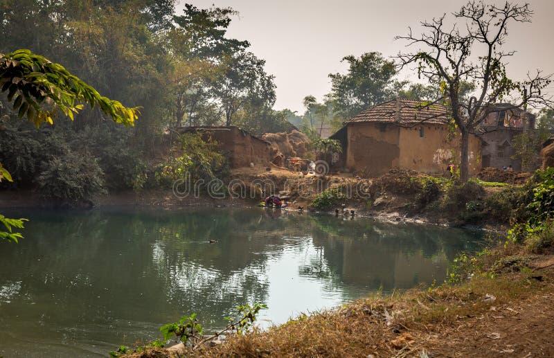 Toneeldiedorpsvijver met eenden het zwemmen met modderhuizen bij een Indisch dorp wordt omringd stock foto's