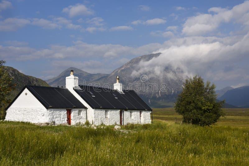 Toneelglencoe met mooi wit huis - Croft in de Schotse Hooglanden, Schotland stock foto's