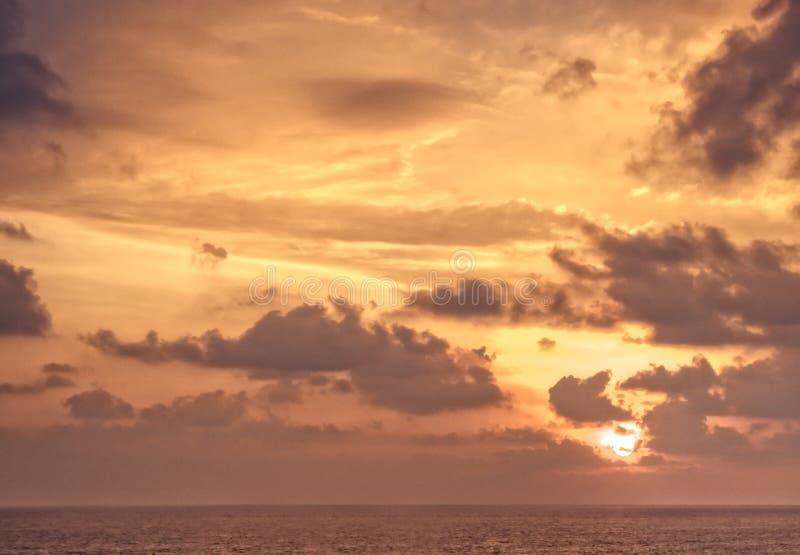 Toneelhemelzonsondergang met zon overzeese horizon met wolken oranje achtergrond stock foto's