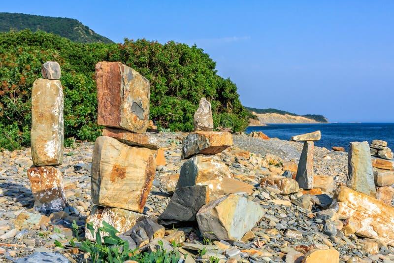 Toneellandschap van de kust van de Zwarte Zee door Bolshoy Utrish dorp, Anapa, Rusland Steentorens op kiezelsteenstrand op blauwe royalty-vrije stock foto's