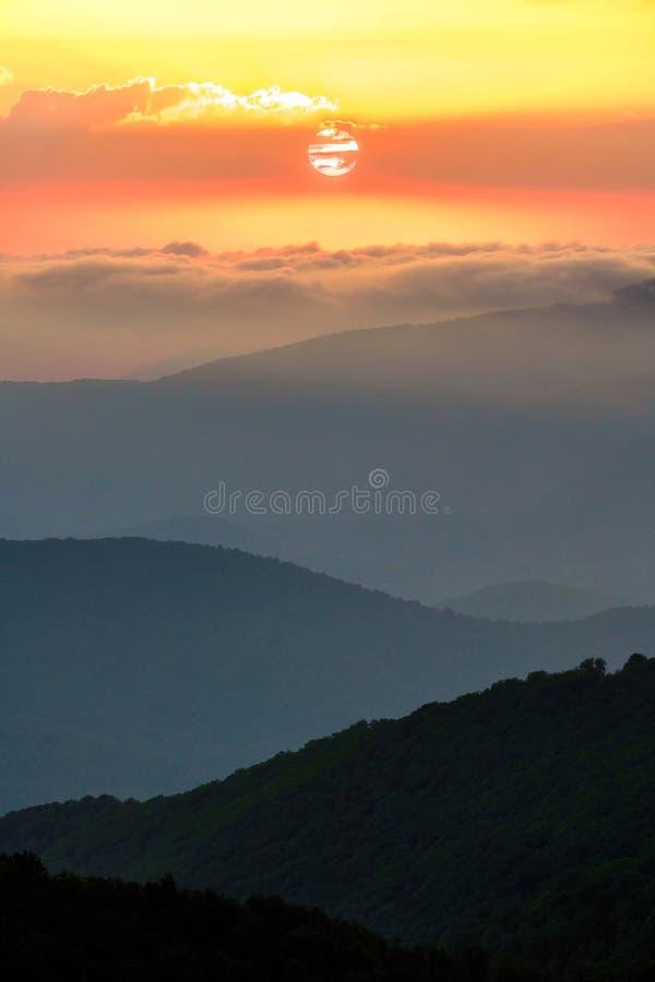 Toneellandschap van de zomerzonsondergang in de bergen van de Kaukasus Zon het plaatsen bihind wolken stock afbeelding