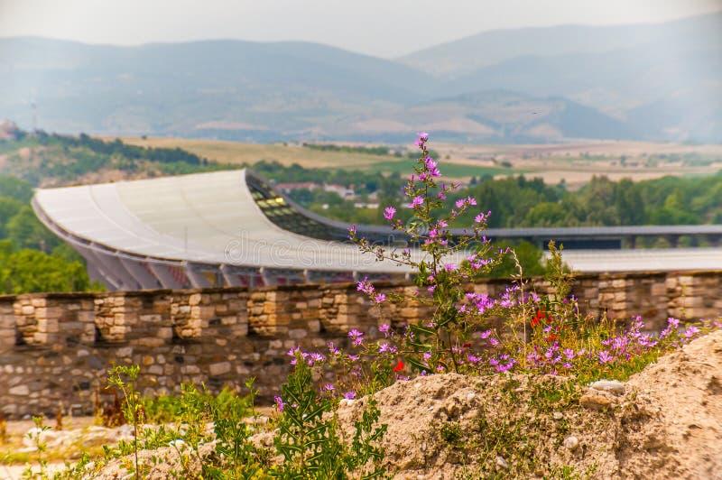 Toneelmening over modern stadion in Skopje die Philip II Nationale Arena met rotsachtig landhoogtepunt van het groeien het bloeie royalty-vrije stock fotografie