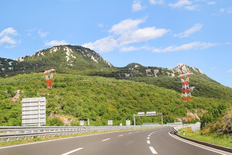 Toneelmening over wegweg die door in Kroatië, Europa/Elektrotransmissietorens, hemel en wolken leiden op achtergrond stock foto's