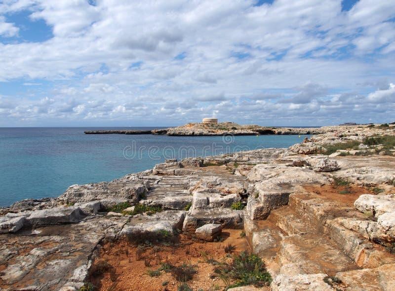 Toneelmening van de baai bij cala santandria in menorca met gesneden klippen en oud fort in de afstand met blauwe de zomerhemel royalty-vrije stock fotografie