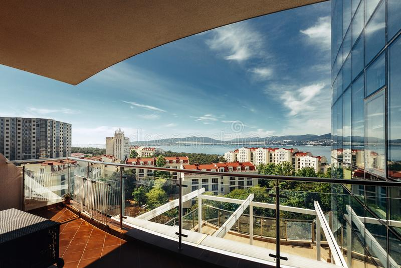 Toneelmening van de stad en het overzees met een terras in een moderne wolkenkrabber met panoramisch royalty-vrije stock fotografie