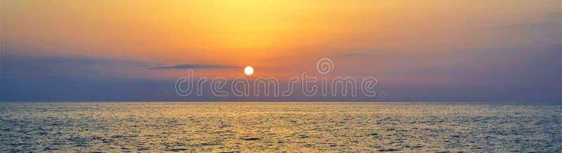 Toneelmening van de sterke zonsondergang bij de kust met indigo blauwe wolken op de oranje hemel stock foto