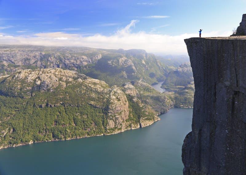 Toneelmening van een wandelaar die zich op Preikestolen bevinden en op de fjord, Noorwegen kijken royalty-vrije stock afbeeldingen