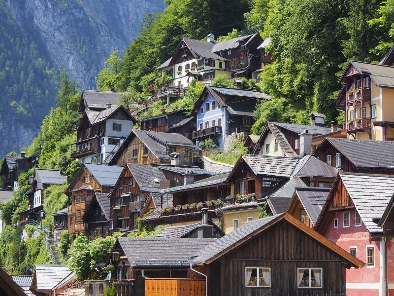 Toneelmening van traditionele oude blokhuizen omhoog de heuvel in beroemd Hallstatt-bergdorp stock afbeelding
