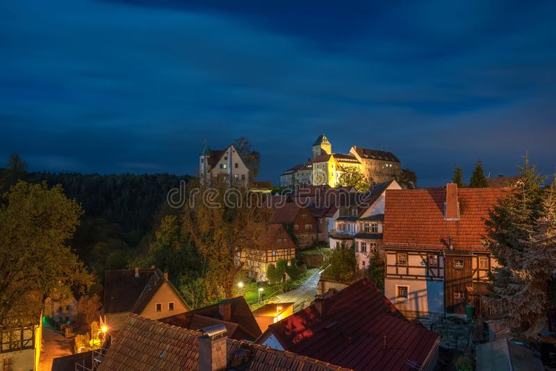 Toneelnacht scape van Hohnstein-stad met Hohnstein-kasteel en keurige hout ontwerpende huizen in Saksisch Zwitserland, Duitsland stock foto