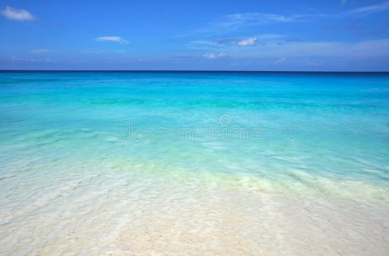 Toneelzeegezicht van azuurblauw transparant oceaanwater en blauwe hemel Tropisch strand met wit zand Idyllisch landschap van kust stock afbeelding