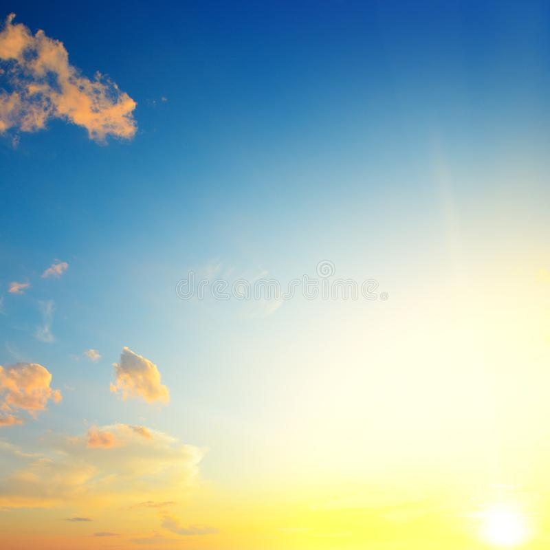 Toneelzonsondergang met zonstralen tegen heldere blauwe hemel stock afbeelding