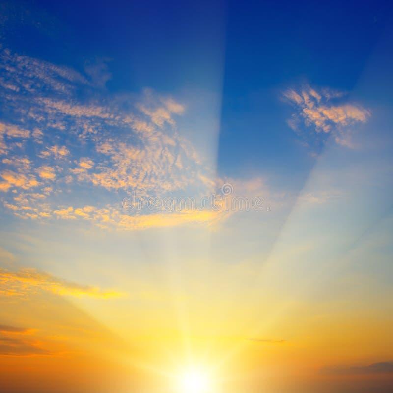 Toneelzonsondergang met zonstralen tegen heldere blauwe hemel stock foto's