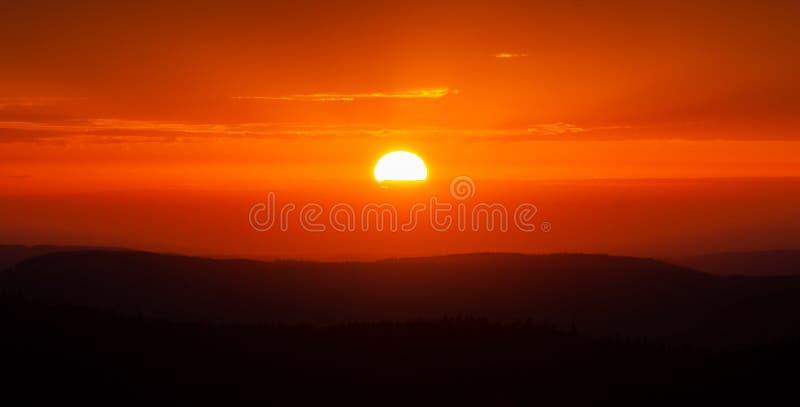 Toneelzonsondergang over bergen Gloeiende zon en oranje hemel en bergketenlandschap royalty-vrije stock foto