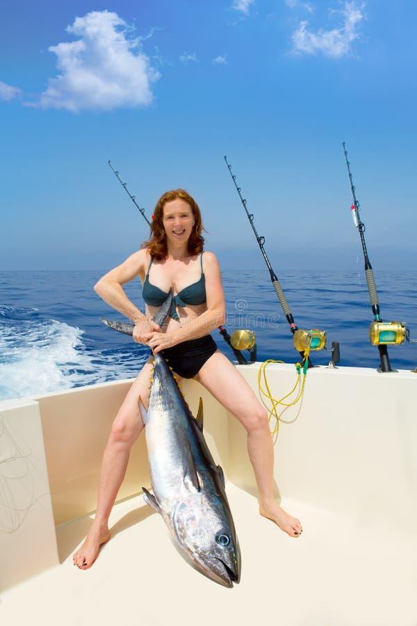 Tonfisk för bluefin för holding för bikinifisherkvinna på fartyget arkivbild