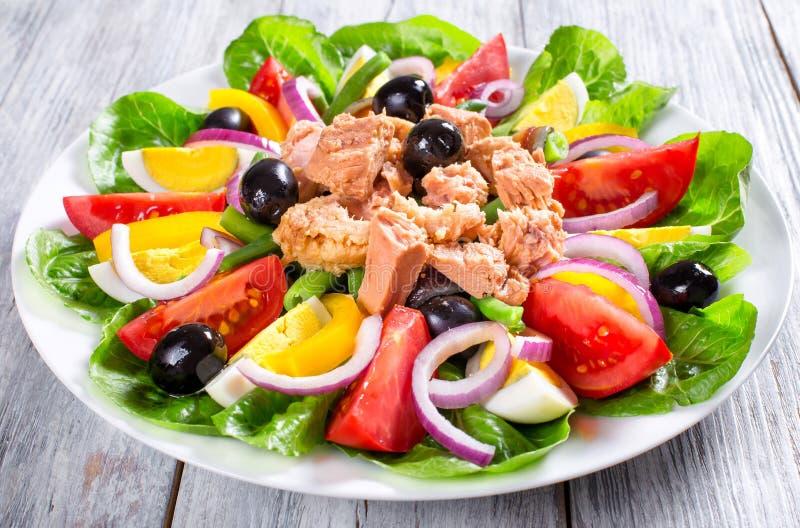 Tonfisksallad med ansjovisar, ägg, svarta oliv, tomater, olja, basilika, vitlök, vinäger royaltyfria bilder