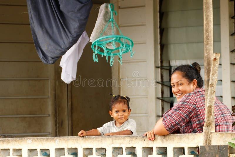 Tongaanse vrouw met een kindzitting op een voorportiek van haar huis, stock afbeeldingen