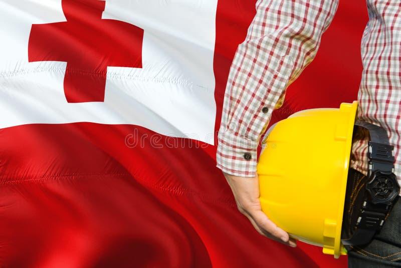 Tongan inżynier trzyma żółtego zbawczego hełm z machać Tonga chorągwianego tło Budowy i budynku poj?cie zdjęcie royalty free