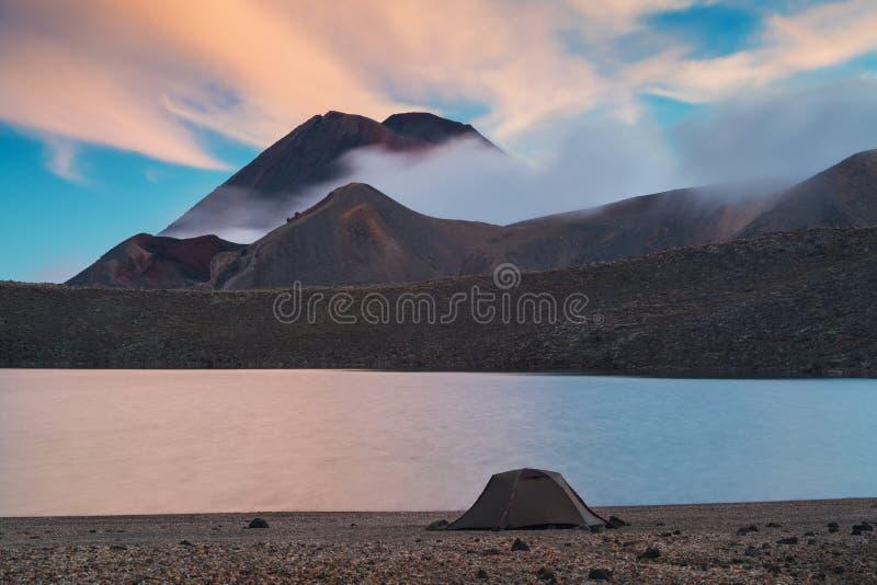 Tongariro alpine crossing, Blue lake. Early morning sunrise, landscape scenery of blue lake, wild mountains and huge volcano. royalty free stock image