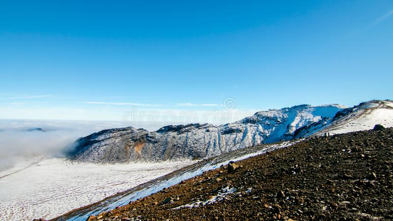 Volcanic rocks landscape above the clouds, climbing from South Crater to Red Crater, view of snow covered volcanic mountains royalty free stock photo