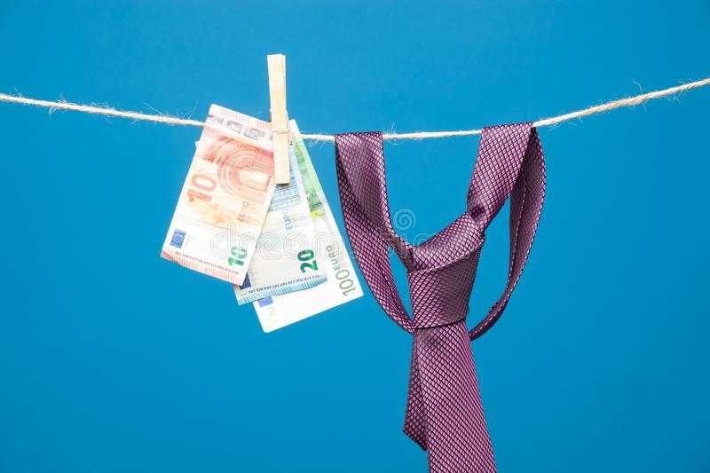 Tongs, money and tie with knot, on a rope. Money hanging on a rope and held by a wooden clamp, a clothespin and hanging clothes. Ticket of legal tender, money in royalty free stock photo
