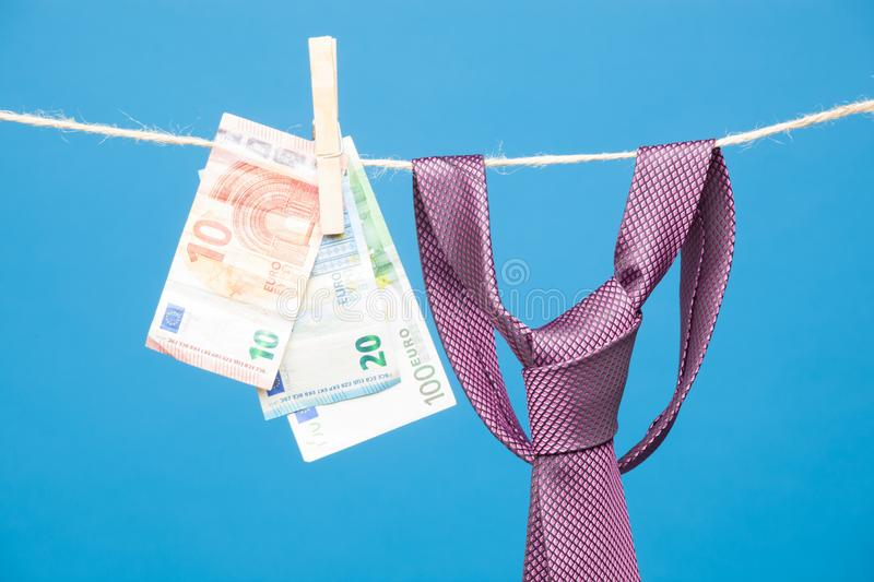 Tongs, money and tie with knot, on a rope. Money hanging on a rope and held by a wooden clamp, a clothespin and hanging clothes. Ticket of legal tender, money in stock photo