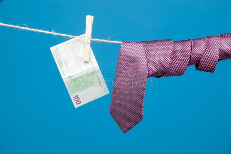 Tongs, money and tie with knot, on a rope. Money hanging on a rope and held by a wooden clamp, a clothespin and hanging clothes. Ticket of legal tender, money in stock images