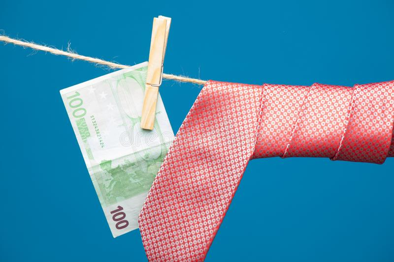 Tongs, money and tie with knot, on a rope. Money hanging on a rope and held by a wooden clamp, a clothespin and hanging clothes. Ticket of legal tender, money in stock photography