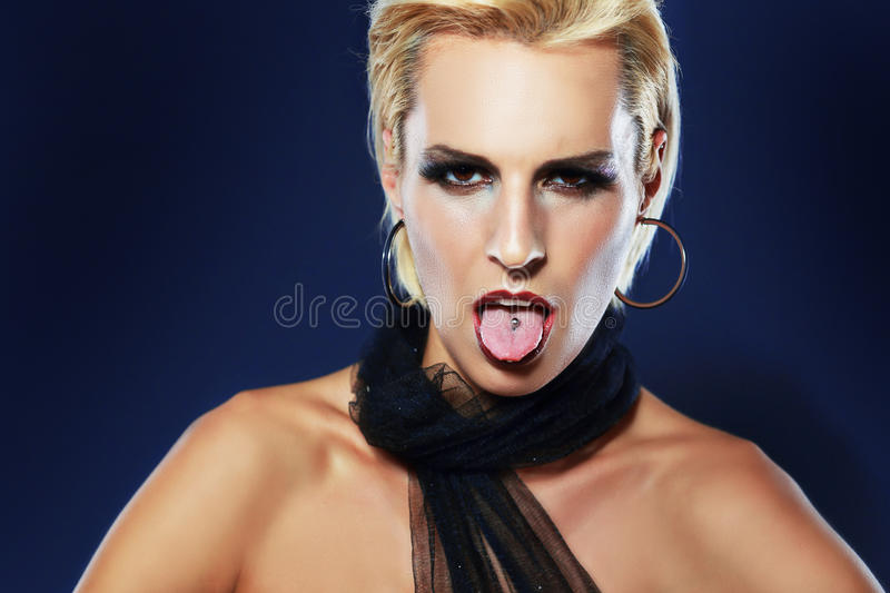 Tongue with piercing. Young woman showing het tongue with piercing stock images