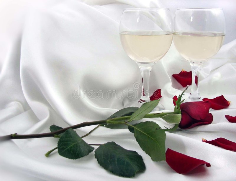 Tonight. Crystal wine glasses and a long-stem rose on white satin bedsheets royalty free stock photos