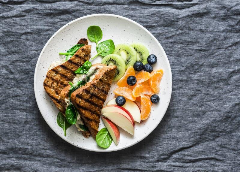 Tonijn, spinazie, mozarella hete toost en vers fruit - heerlijk gezond ontbijt, brunch, snack op een grijze achtergrond royalty-vrije stock afbeelding