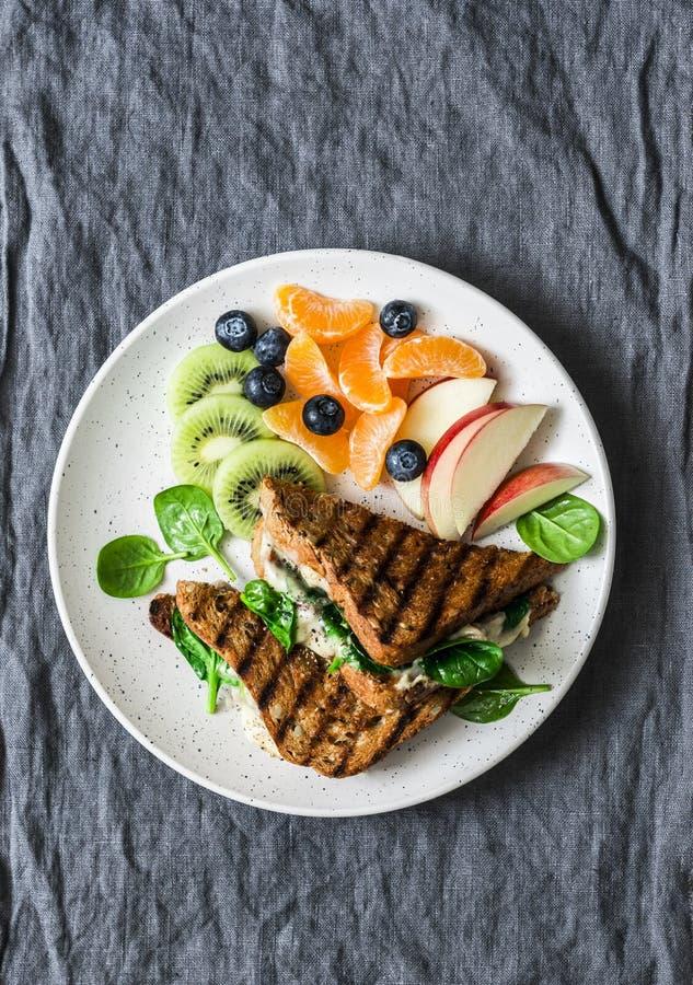 Tonijn, spinazie, mozarella hete toost en vers fruit - heerlijk gezond ontbijt, brunch, snack op een grijze achtergrond royalty-vrije stock afbeeldingen