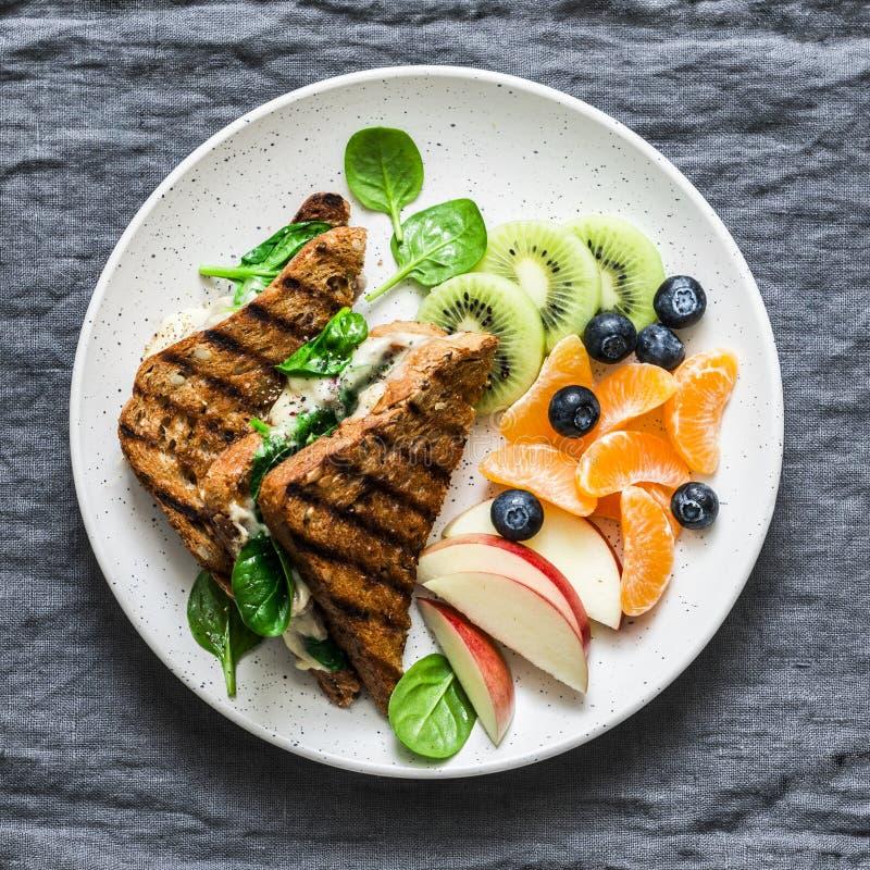 Tonijn, spinazie, mozarella hete toost en vers fruit - heerlijk gezond ontbijt, brunch, snack op een grijze achtergrond, hoogste  stock foto's