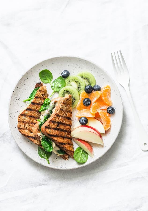Tonijn, spinazie, mozarella hete toost en vers fruit - heerlijk gezond ontbijt, brunch, snack op een lichte achtergrond stock afbeelding