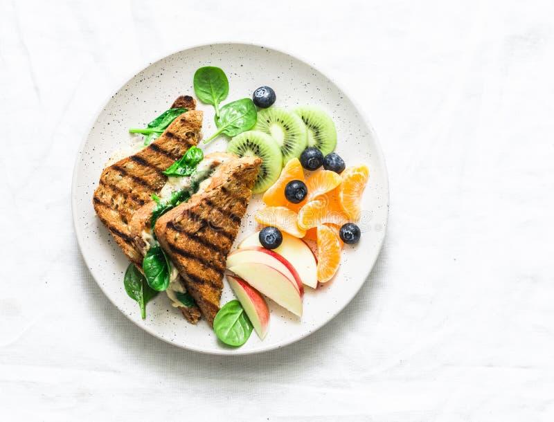 Tonijn, spinazie, mozarella hete toost en vers fruit - heerlijk gezond ontbijt, brunch, snack op een lichte achtergrond royalty-vrije stock afbeelding