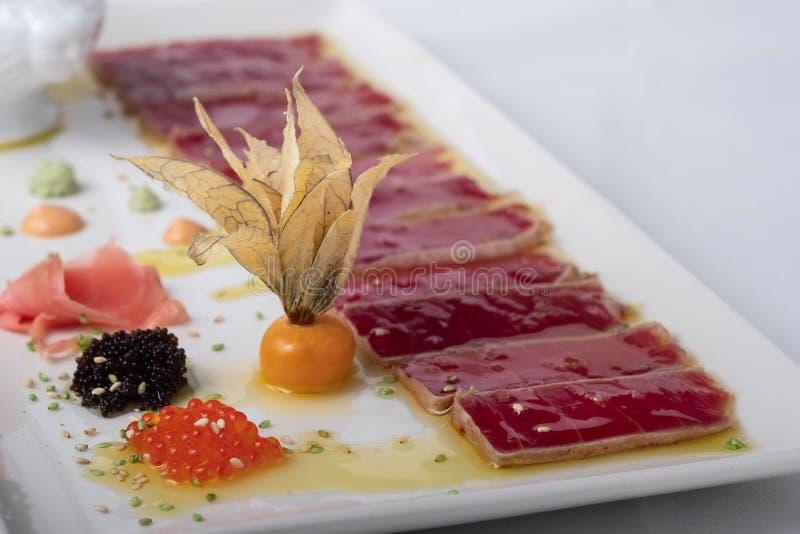 Tonijntataki op olijfolieachtergrond gecombineerd met kaviaar stock foto