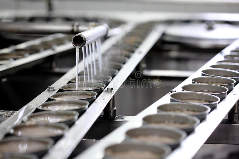 Tonijnvissen in blikverwerking in fabriek stock afbeelding