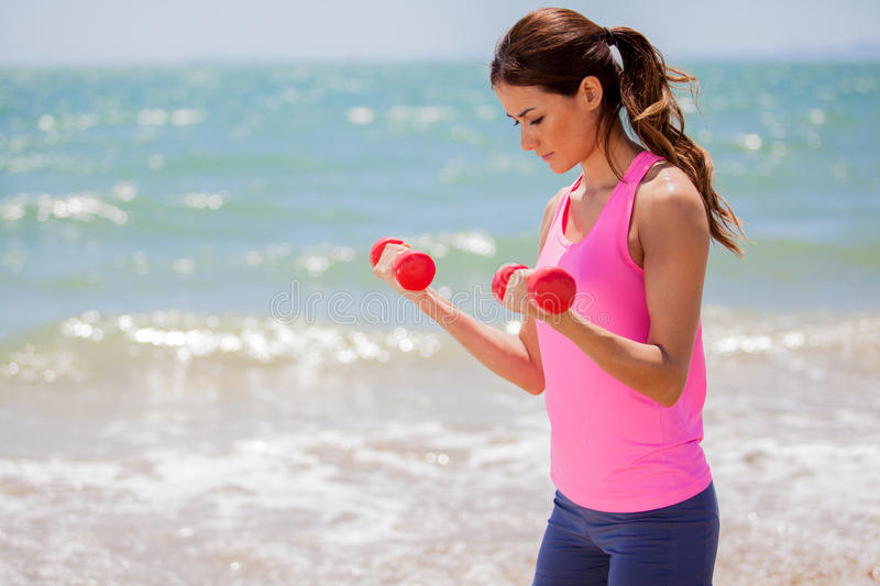 Toning muscles at the beach. Pretty Latin brunette lifting weights at the beach royalty free stock image