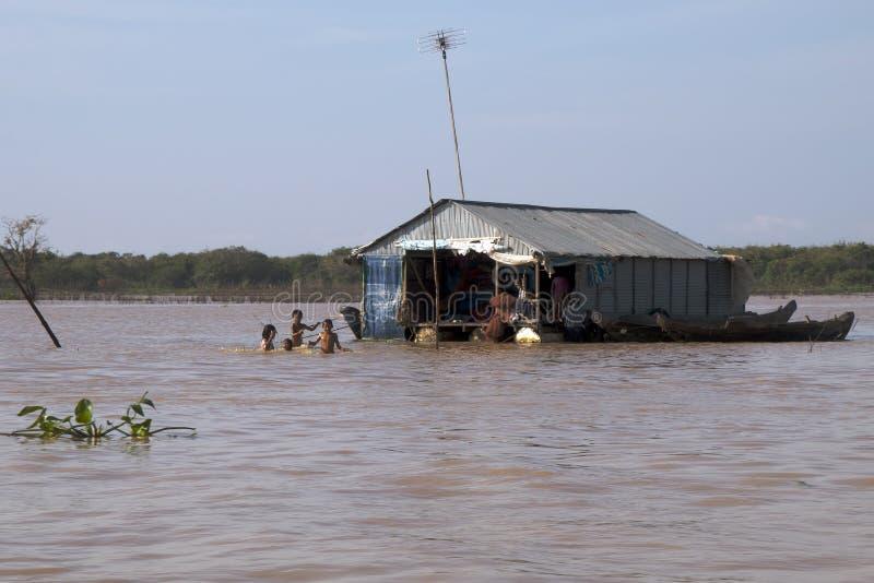 Tonle underminerar Cambodja Januari 4 2018, traditionellt husfartyg med barn som spelar i lerigt vatten royaltyfria bilder