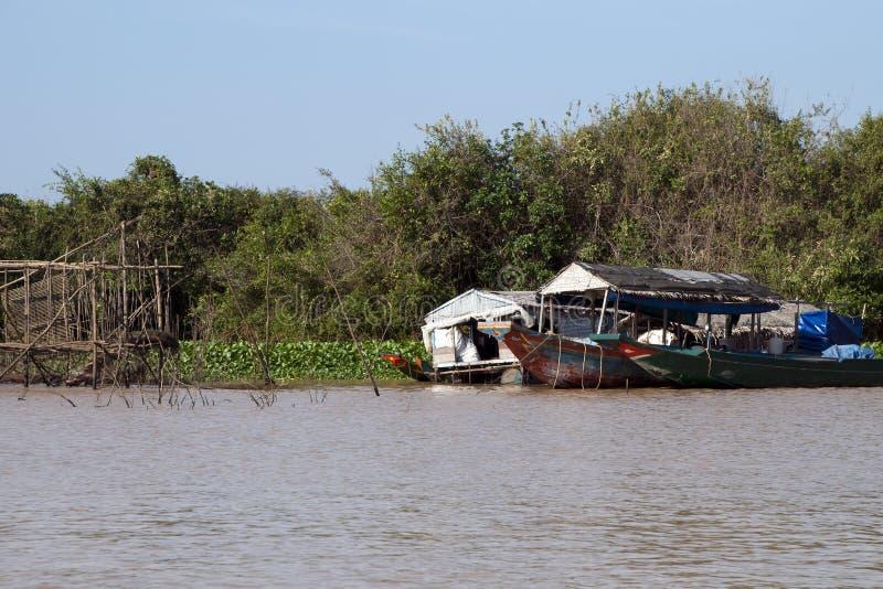 Tonle underminerar sjöfloodplainen med husbåten nära en träfiskestruktur royaltyfri foto
