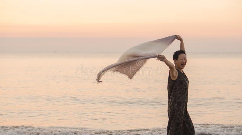 Tonne supérieure asiatique heureuse de femme à la plage avec le tissu d'écharpe et l'espace de copie photos stock