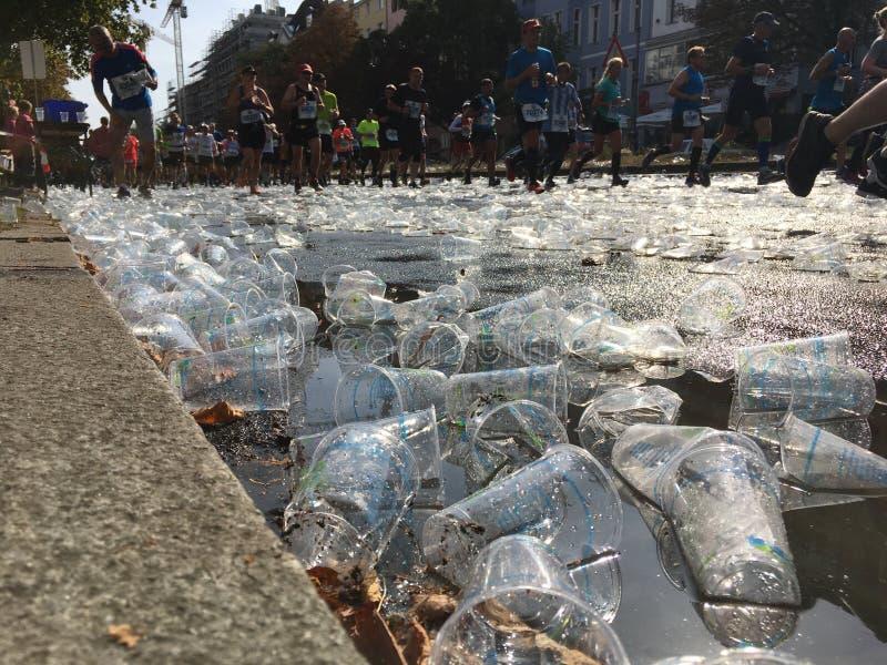 Tonnen leere Plastikschalen-Leute, die vorbei bei Berlin Marathon laufen stockfotografie