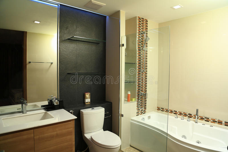 Tono caldo di progettazione di interni di lusso del bagno con la Jacuzzi immagine stock libera da diritti