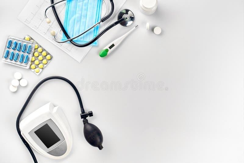 Tonometer bonde branco com estetoscópio, os comprimidos coloridos, a máscara e o termômetro na tabela branca Vista superior fotografia de stock