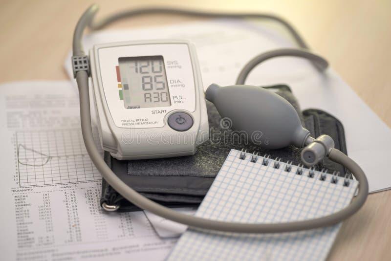 Tonometer e bloco de notas no fundo dos gráficos e dos diagnósticos médicos, lugar para o texto fotos de stock royalty free
