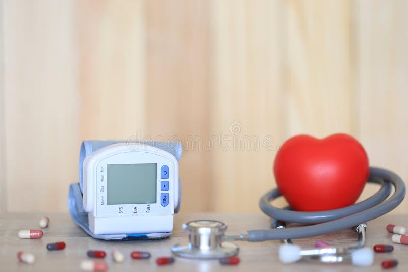 Tonometer médico para a pressão sanguínea de medição com estetoscópio e coração vermelho no fundo do wooder, em despesas médicas  fotos de stock