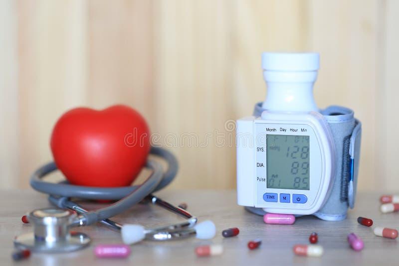 Tonometer médico para a pressão sanguínea de medição com estetoscópio e coração vermelho no fundo do wooder, em despesas médicas  foto de stock
